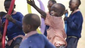 КЕНИЯ, KISUMU - 20-ОЕ МАЯ 2017: Счастливые африканские дети играя с воздушными шарами снаружи в солнечном дне сток-видео