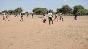 КЕНИЯ, KISUMU - 20-ОЕ МАЯ 2017: Счастливые африканские дети и учитель курсируя футбол снаружи после школы сток-видео