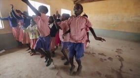 КЕНИЯ, KISUMU - 20-ОЕ МАЯ 2017: Счастливые африканские дети повторяя движения танцев после кавказских людей акции видеоматериалы