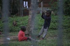 КЕНИЯ, KISUMU - 23-ЬЕ МАЯ 2017: Взгляд через загородку Группа в составе африканские люди тратя время снаружи Маленькие ребята име стоковое фото rf