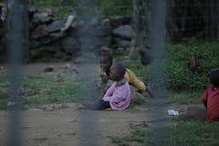 КЕНИЯ, KISUMU - 23-ЬЕ МАЯ 2017: Взгляд через загородку Группа в составе африканские люди тратя время снаружи Маленькие ребята име стоковое фото
