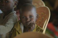 КЕНИЯ, KISUMU - 23-ЬЕ МАЯ 2017: Портрет счастливого африканского мальчика сидя внутрь с группой в составе дети и танцуя, усмехаяс стоковая фотография