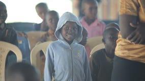 КЕНИЯ, KISUMU - 23-ЬЕ МАЯ 2017: Портрет счастливого африканского мальчика сидя внутрь с группой в составе дети и танцуя, усмехаяс стоковое фото