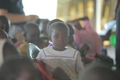 КЕНИЯ, KISUMU - 23-ЬЕ МАЯ 2017: Портрет счастливого африканского мальчика сидя внутрь с группой в составе дети и танцуя, усмехаяс стоковое фото rf