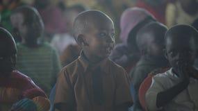 КЕНИЯ, KISUMU - 23-ЬЕ МАЯ 2017: Портрет счастливого африканского мальчика сидя внутрь с группой в составе дети и танцуя, усмехаяс стоковое изображение rf