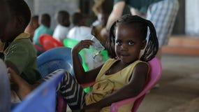 КЕНИЯ, KISUMU - 23-ЬЕ МАЯ 2017: Портрет счастливой африканской девушки сидя внутрь с группой в составе дети и танцуя, усмехаясь стоковые фотографии rf