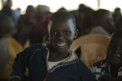 КЕНИЯ, KISUMU - 23-ЬЕ МАЯ 2017: Портрет счастливой африканской девушки сидя внутрь с группой в составе дети и танцуя, усмехаясь стоковая фотография