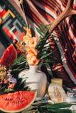 Керамическая ваза с цветками, рожками, отрезала дыни и листья арбуза и ладони на предпосылке красной ткани заплатки Стоковые Изображения RF