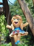Керамическая кукла девушки Smiley на качании Стоковая Фотография RF