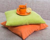Керамическая оранжевая чашка с лимоном половинным на поддоннике на куче от Стоковое Фото