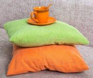 Керамическая оранжевая чашка с поддонником на куче от зеленого цвета и апельсина Стоковое Изображение