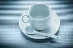 Керамическая чайная ложка поддонника чашки на striped предпосылке Стоковое Фото