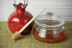 Керамические гранатовое дерево и бак меда на дерюге Стоковые Фото