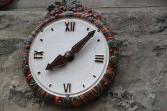 Керамические настенные часы на серой стене Стоковая Фотография