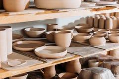 керамические плиты и шары на деревянных полках в мастерской гончарни Стоковая Фотография RF