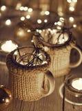 Керамические стильные чашки в свитерах и гирлянде рождества ретро на предпосылке светов bokeh поле глубины отмелое Подкрашиванное Стоковые Изображения
