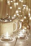 Керамические стильные чашки в свитерах и гирлянде рождества ретро на предпосылке светов bokeh поле глубины отмелое Подкрашиванное Стоковое Изображение