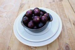 Керамические шар и плита с черными виноградинами scuppernong muscadine стоковое фото