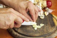 Керамический нож прерывая варить подготовки чеснока Чеснок, ароматичные ингридиенты для приправляя еды Стоковая Фотография RF