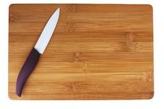 Керамический нож с фиолетовой ручкой на разделочной доске Стоковое фото RF