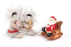 Керамический Санта Клаус читает книгу в стуле близко Стоковая Фотография
