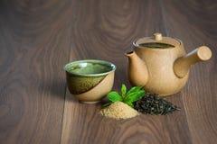 Керамический чайник, чашка черного чая с листьями мяты и желтый сахарный песок на деревянном столе Стоковые Изображения RF