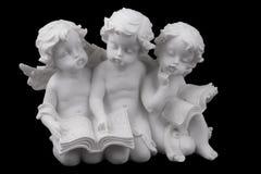 3 керамических белых ангела прочитали книгу, мечтая и думая Стоковые Изображения