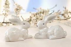 2 керамических зайчика перед вишневыми цветами, концом-вверх Стоковое Изображение RF