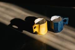 2 керамических чашки для кофе Один голубой цвет цвета одного желтый стоковые фотографии rf