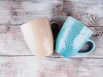 2 керамических чашки с сердцами на деревянной предпосылке Стоковое Изображение