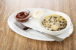 Кетчуп и майонез, julienne с цыпленком и гриб в шаре, вилке в блюде на дерев стоковое фото