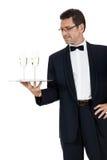 Кельнер взрослого мужчины служа 2 изолированного стекла шампанского Стоковое Фото