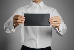 Кельнер в белой рубашке держа пустую ясную черноту она стоковые фото