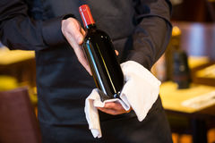 Кельнер держа бутылку красного вина Стоковые Фото