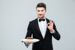 Кельнер держа плиту с тортом и показывая одобренный знак Стоковые Изображения RF