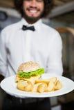 Кельнер держа плиты картофельной стружки и бургера в баре Стоковое фото RF