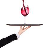 Кельнер держа серебряный поднос с красным вином стоковая фотография rf