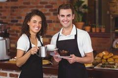 Кельнер и официантка усмехаясь на камере стоковое фото rf