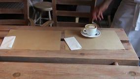 Кельнер кладет 2 чашки кофе на таблицу видеоматериал
