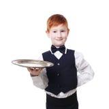 Кельнер мальчика стоит с пустой сервировкой подноса что-то Стоковые Изображения RF