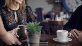Кельнер носит большую чашку капучино для молодых пар на подносе, который выполняет аперитив в ресторане, a видеоматериал
