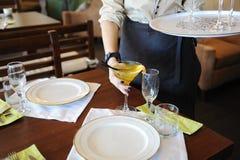 Кельнер принимает на коктеиль желтого цвета таблицы плиты ставят белизну на обсуждение Стоковые Фото