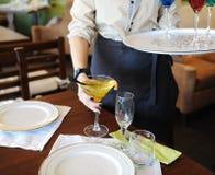 Кельнер принимает на коктеиль желтого цвета таблицы плиты ставят белизну на обсуждение Стоковое Изображение