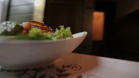 Кельнер приносит очень вкусное свежее блюдо салата к таблице на подносе сток-видео