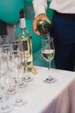 Кельнер льет вино в стекла на таблице шведского стола Стоковые Изображения