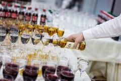 Кельнер льет виски в стекло стекла на белом tabl Стоковые Изображения RF