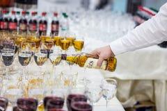 Кельнер льет виски в стекло стекла на белом tabl Стоковые Изображения