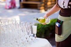 Кельнер льет шампанское в стекло Пустые стекла на whi Стоковое Изображение