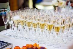 Кельнер льет шампанское в стекло Стекла на белой плате Стоковые Изображения