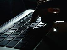 Кибернетическое преступление - одна рука на клавиатуре в темноте Стоковые Фотографии RF
